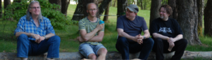 Vier Männer sitzen auf einem Baumstamm